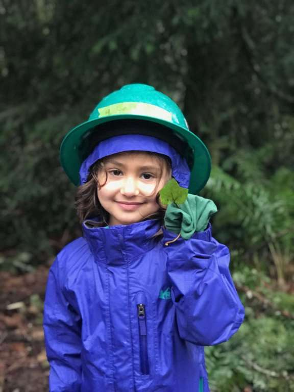 A young girl in a green hardhat holds up an ivy leaf.