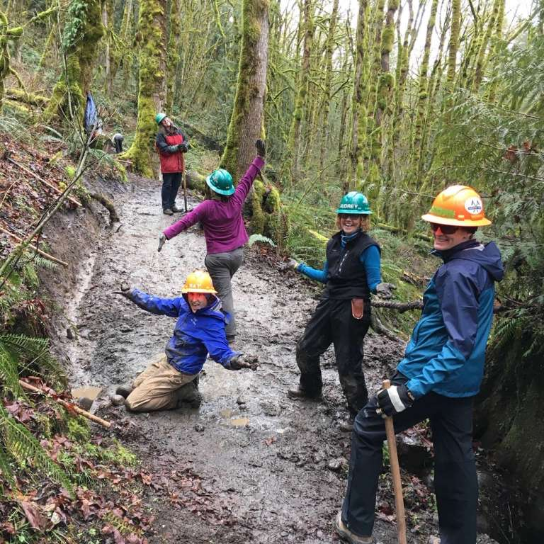 Five women on a muddy trail with a newly dug ditch leading to a culvert under the trail.