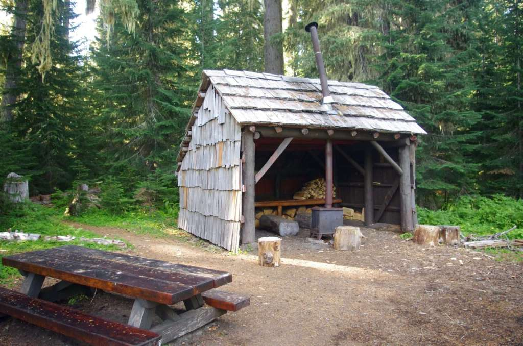 A three-sided wooden shelter and a picnic table.