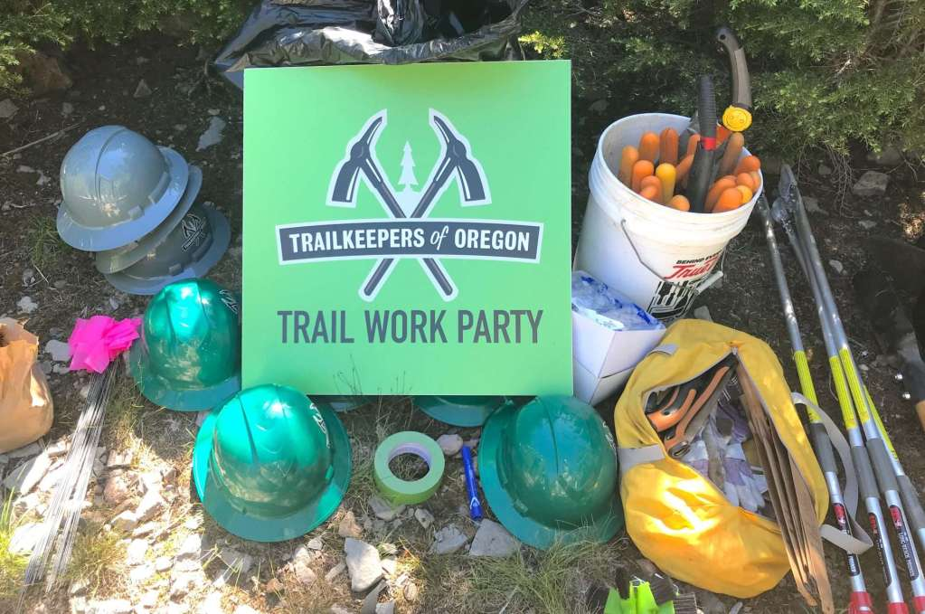 "A TKO ""Trail Work Party"" sign surrounded by hardhats, gloves, loppers, and other trail tools."