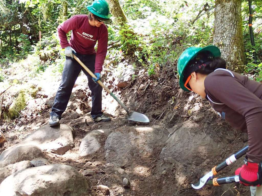 Two workers, one with a shovel and one with loppers, working on a section of trail that has more boulders than dirt.