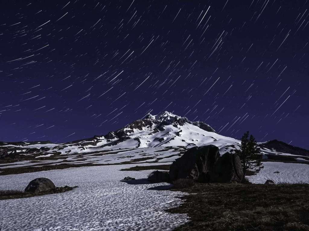 Star trails in a dark night sky appear above a snowy mountain peak.