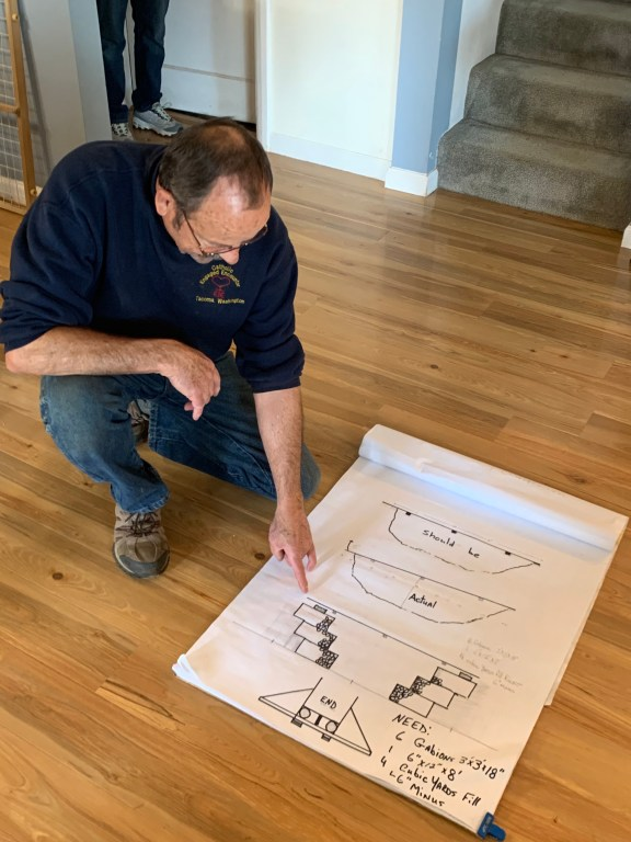 A man points to a large sheet of paper with diagrams on it.