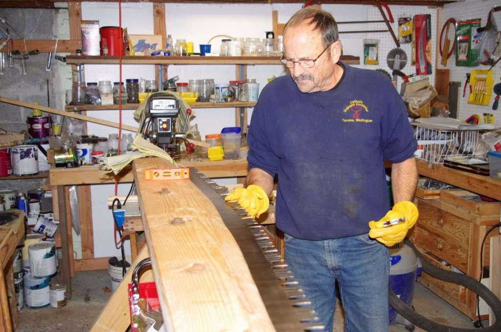 A man with leather gloves on his hands feels the teeth of a long sawblade.
