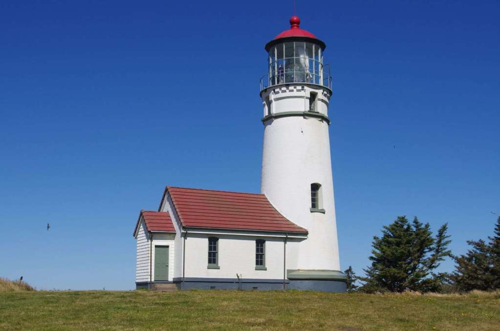 A white lighthouse with a red roof.