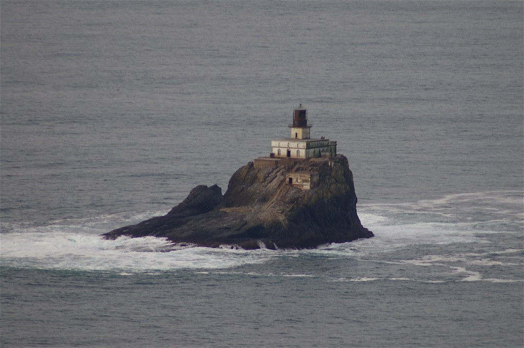 A small lighthouse on a rock in the ocean.