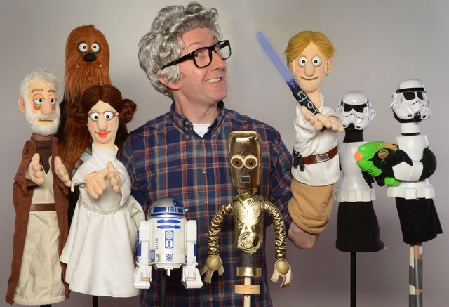 man smiling with Star Wars puppets