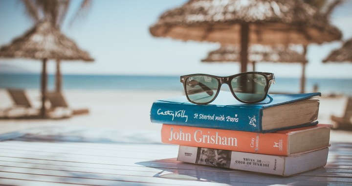 books stacked near a beach with sunglasses on top