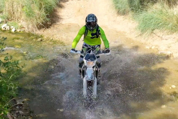 Off-road motorcycle tours riding through trails in remote locations such as single track, desert trails, sand, mountains, rock terrain.