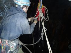 De-rigging the pull through. First untie the Italian hitch and tie an overhand knot on the opposite side of the descent rope. Clip a krab into the overhand knot and the descent rope