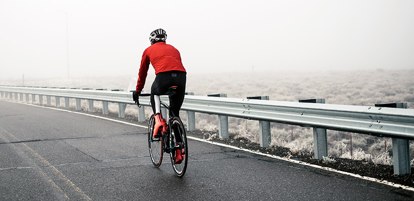 This cyclist is riding outdoors in Winter. When doing a winter cycling training plan outdoors, its essential to have the right clothing.