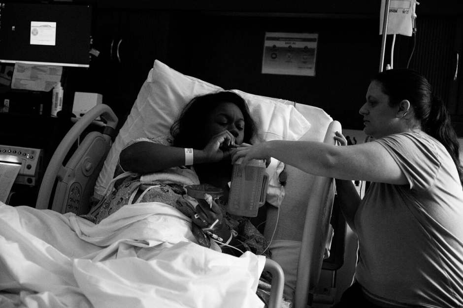 Doula Marissa is giving mother a drink of water