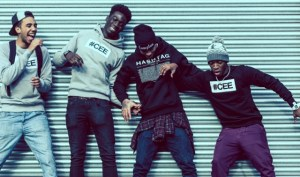 Professional Photography Four Black Men Wearing Hashtagcee And Generals Hoodies And Sweatshirts Pushing And Pulling In Front Of Grey Shutters