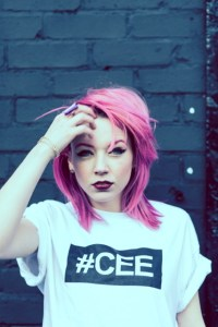 Professional Photography White Woman With Pink Hair Standing In Front Of Black Brick Wall Wearing White Hashtagcee T-Shirt