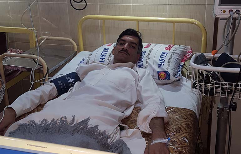 Abdul Salam laying on hospital bed