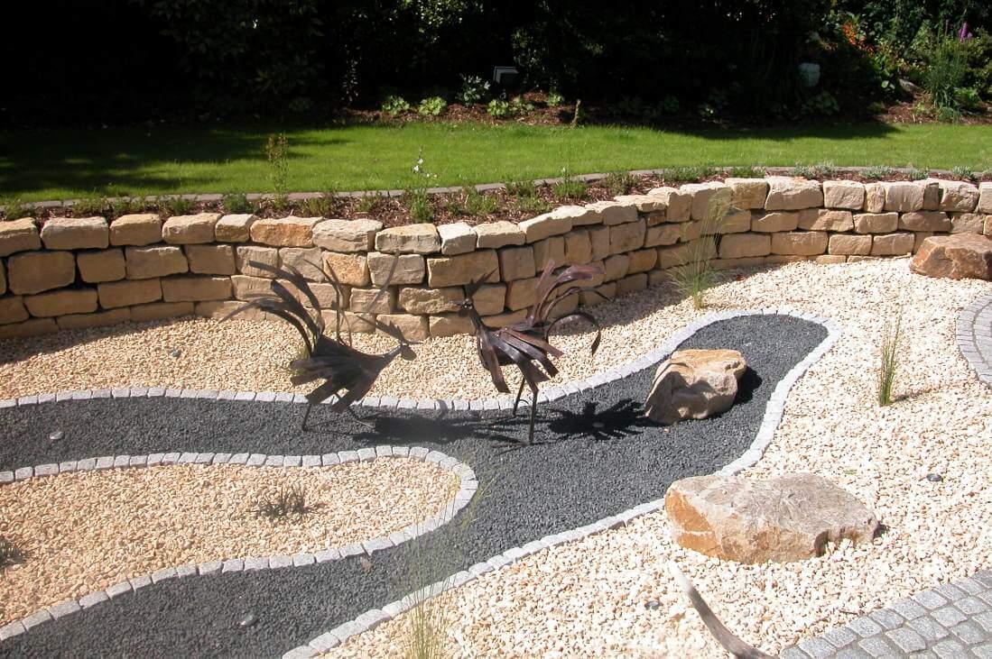 romantischer Garten mit Trockenteich und Brunnen aus Basaltsteelen