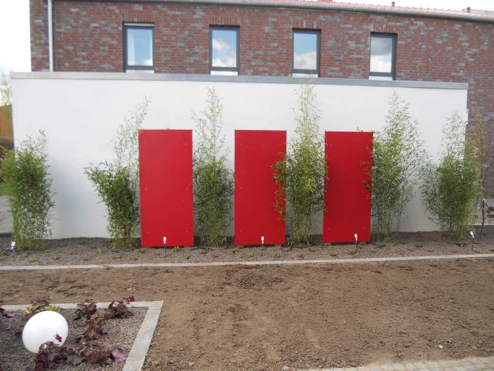 Der Garten erhält sein Grün -Die Bambus erhalten eine farbliche Akzentuierung aus roten Resopalplatten