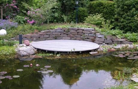 Natursteinmauer mit Sitzplatz in Wassernähe