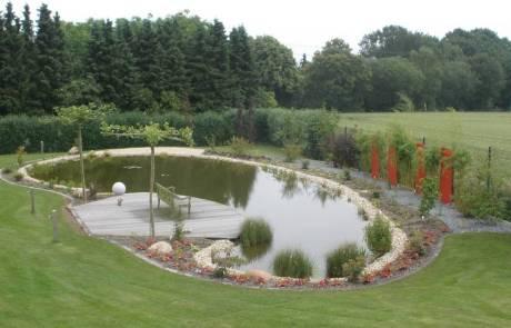 Großer Naturteich mit Holzterrasse über dem Wasser