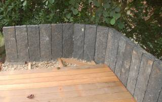 Einfassung einer Holzterrasse aus spaltrauhen Basaltpalisaden