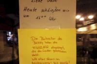 """Zwei Zettel an der Tür des Lokals, wo ab 18h die Finissage stattfinden sollte: Erster Zettel """"Liebe Gäste, heute schließen wir um 16 Uhr"""", drunter zweiter Zettel: """"Die Betreiber haben die Finissage abgesagt, da der Laden geschlossen bleibt. Wir aber feiern im Hesseneck! Mit Musik"""""""