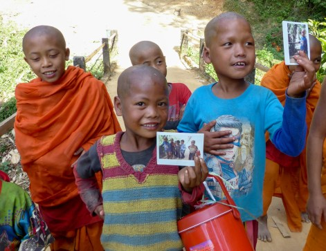 Children and novice monks in a hill tribe village happy about some polaroid pictures
