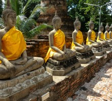 Stone Buddhas in orange dresses in Ayutthaya