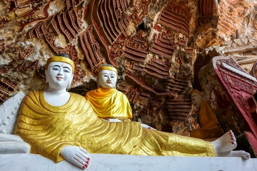 Buddha statues infront of votive tablets decorating the walls of Kawlgoon Cave near Hpa-An
