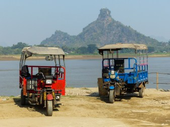 Two Tuk-Tuks parked at the river in front of Hpan Pu Mountain