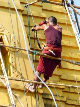 Monk with drilling machine working on the temple roof in Hpa-An