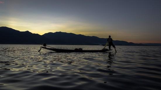 Leg-rowing Intha fisherman before sunrise on Inle Lake