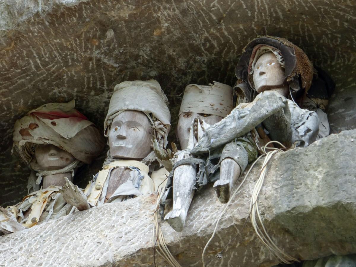 Tana Toraja - wooden figures of the deceased throning over stone graves Christian Jansen & Maria Düerkop