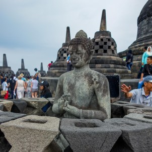 Yogyakarta - Borobodur temples: The encased Buddahs infuse the tourist busy place with a certain calmth. Christian Jansen & Maria Düerkop