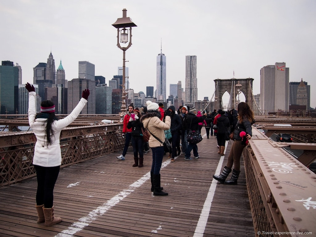 People walking across the Brooklyn Bridge in New York City.