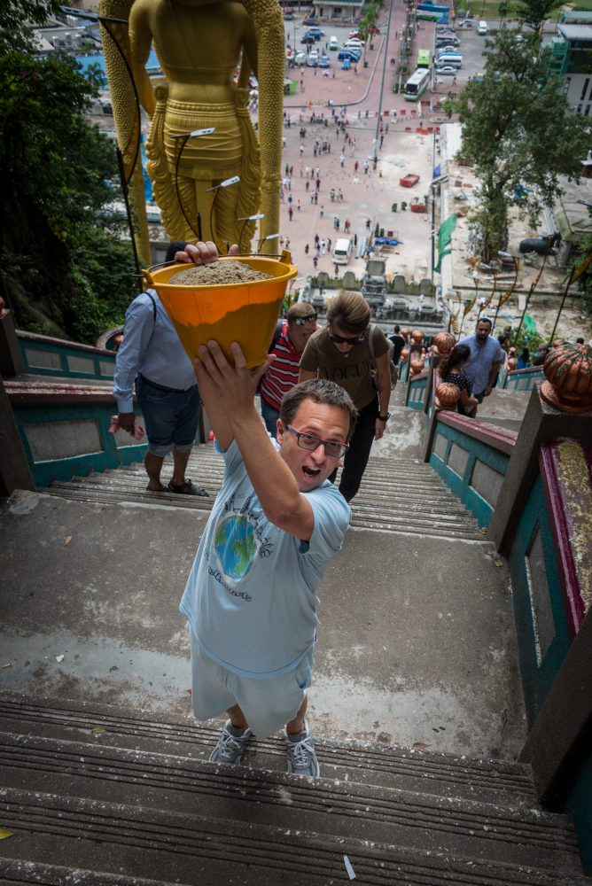 Rick Climbing the stairs with a bucket of sand at the Batu Caves on our Cruise to Asia
