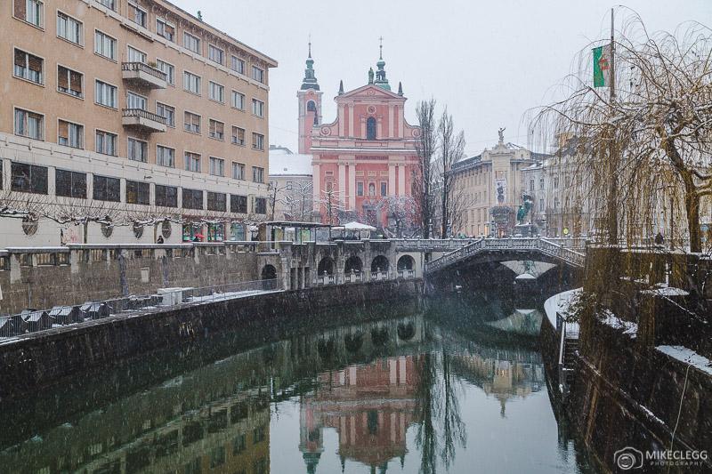 Vistas ao longo de Ljubljanica no inverno com a Igreja Franciscana da Anunciação à distância