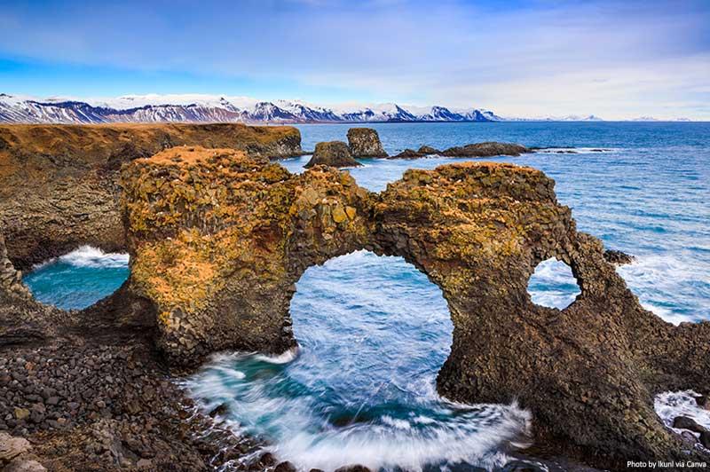 O portão de rocha natural em Arnarstapi, península de Snafellsnes, Islândia
