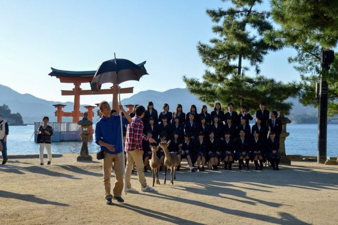 Children and deer posing in front of Itsukushima Shrine, Miyajima, Japan