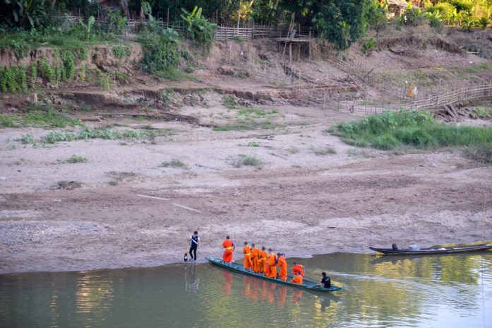 Monks crossing the Nam Khan River by boat in Luang Prabang, Laos