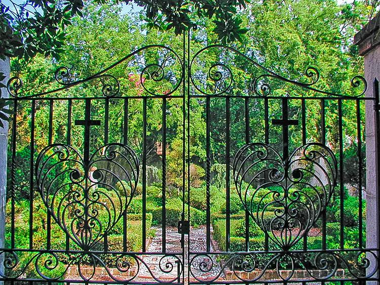 Secret garden in Charleston seen through iron gate