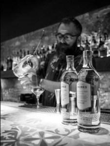 Mezcal Amores bottles and bartender pouring