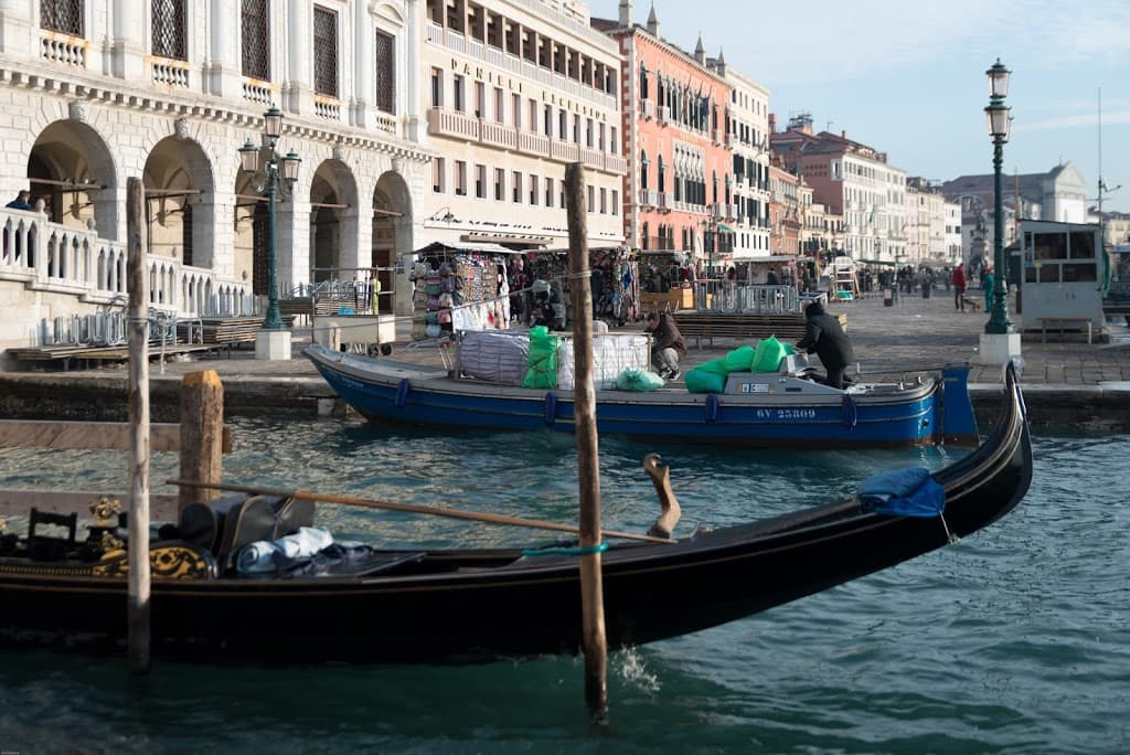 A gondola and a freight boat in Venice Italy