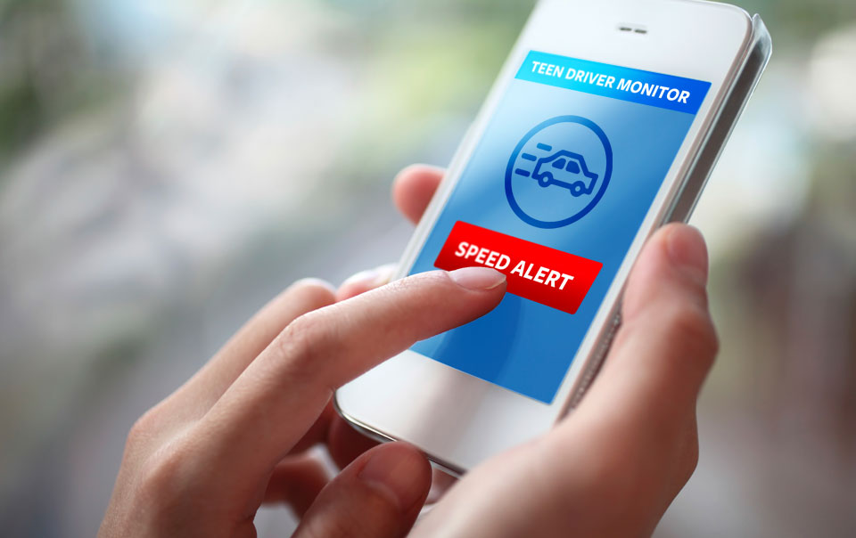 Parent checking teen driver safety app on smartphone