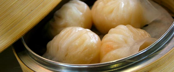 A steaming hot basket of savory har gau dim sum.
