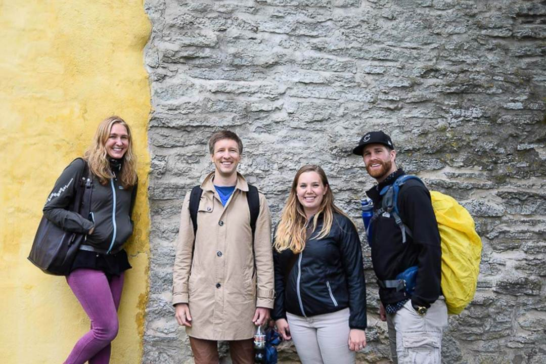 two young couples standing against a yellow wall