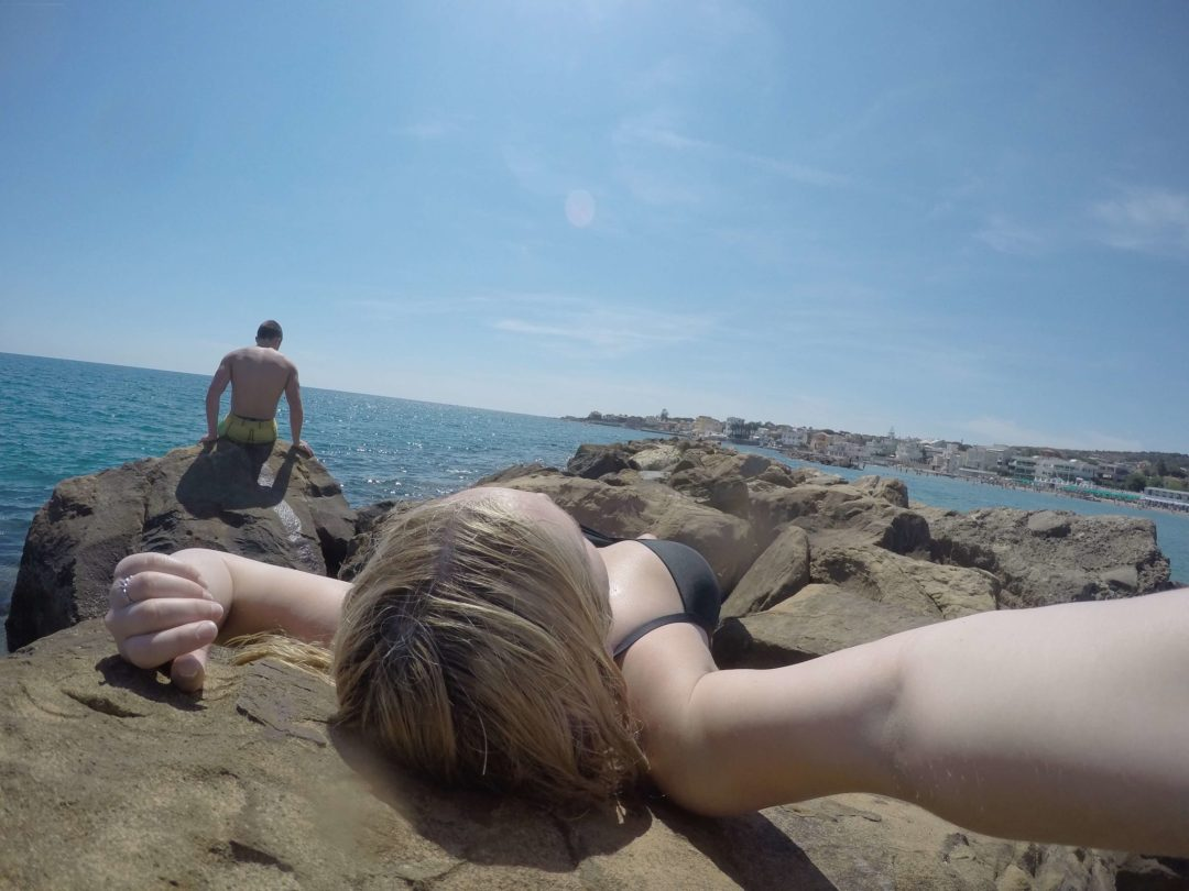 Girl sunbathing on the boulders at Santa Marinella Beach in Italy.