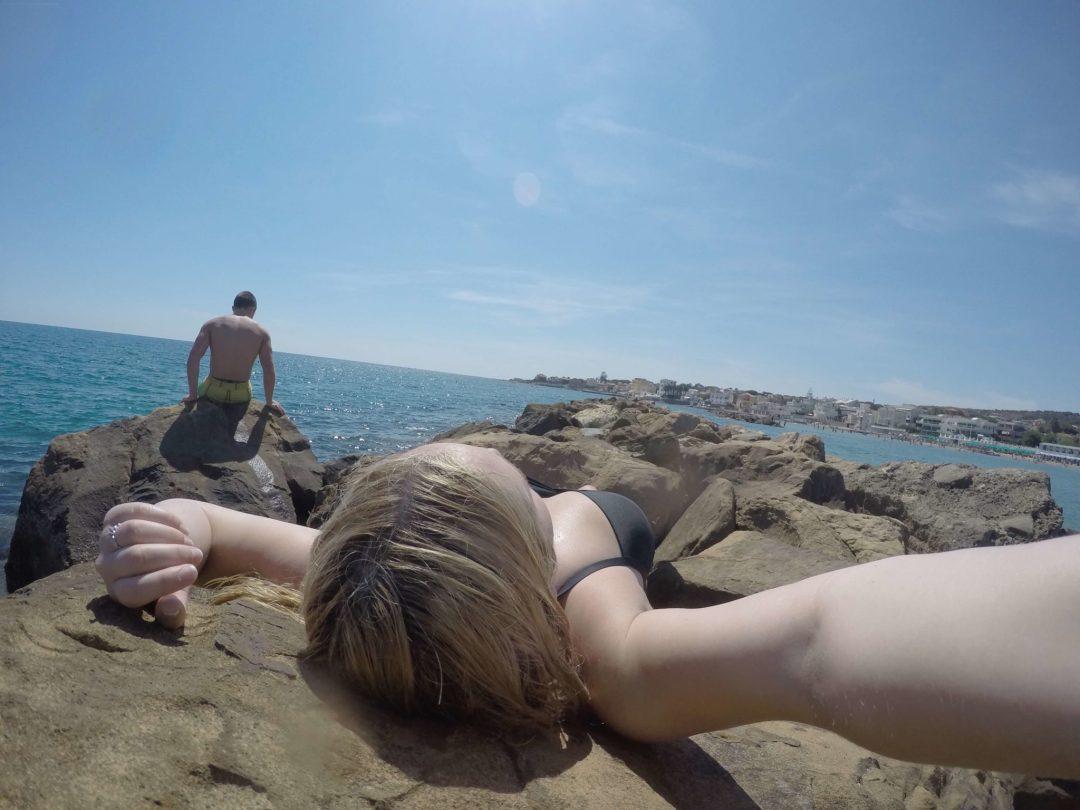 Girl sunbathing on the boulders at Santa Marinella Beach in Italy.