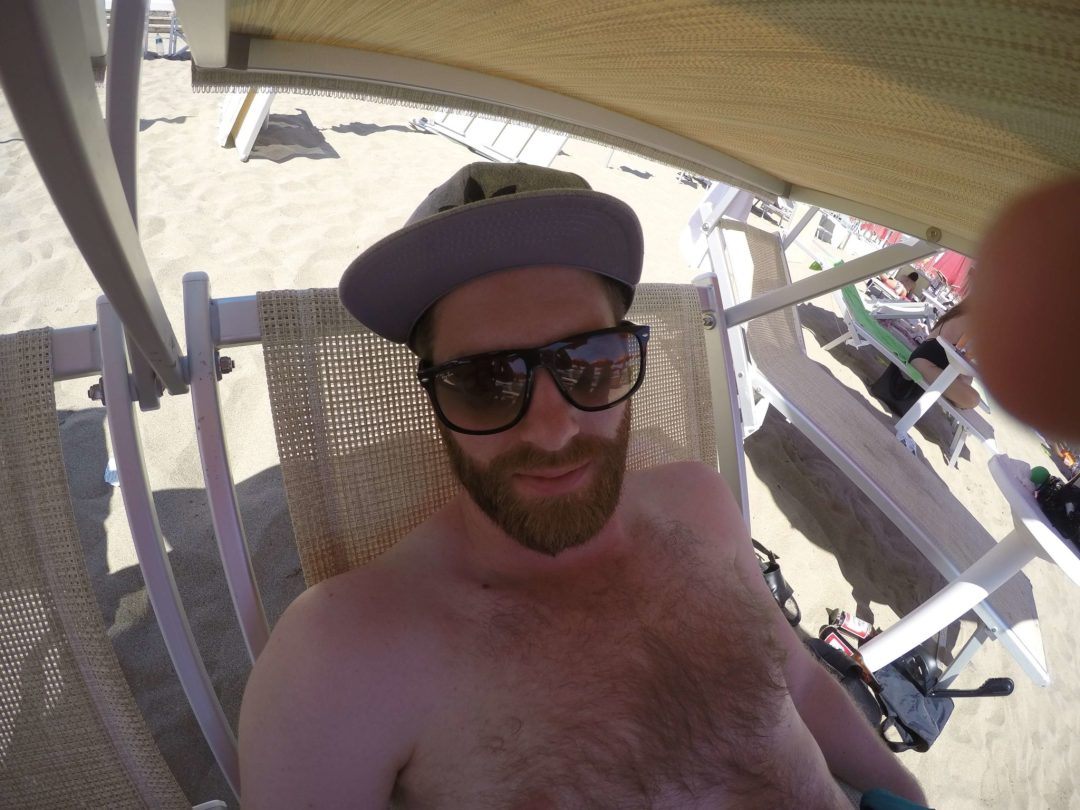 Man with sunglasses, a beard, and a hat sitting under an umbrella at Santa Marinella Beach.