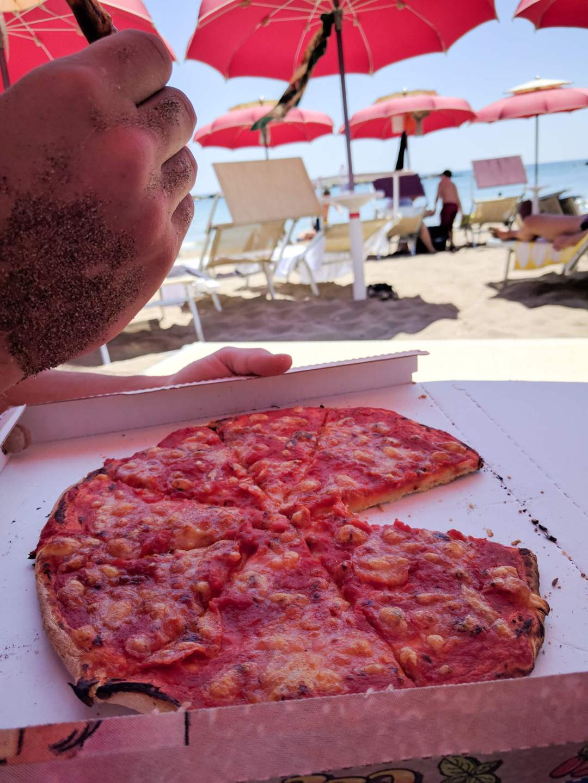 Eating pizza with sandy hands at Santa Marinella Beach