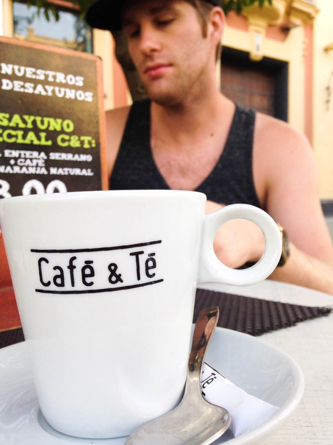 Close-up of a coffee mug with a man in the background